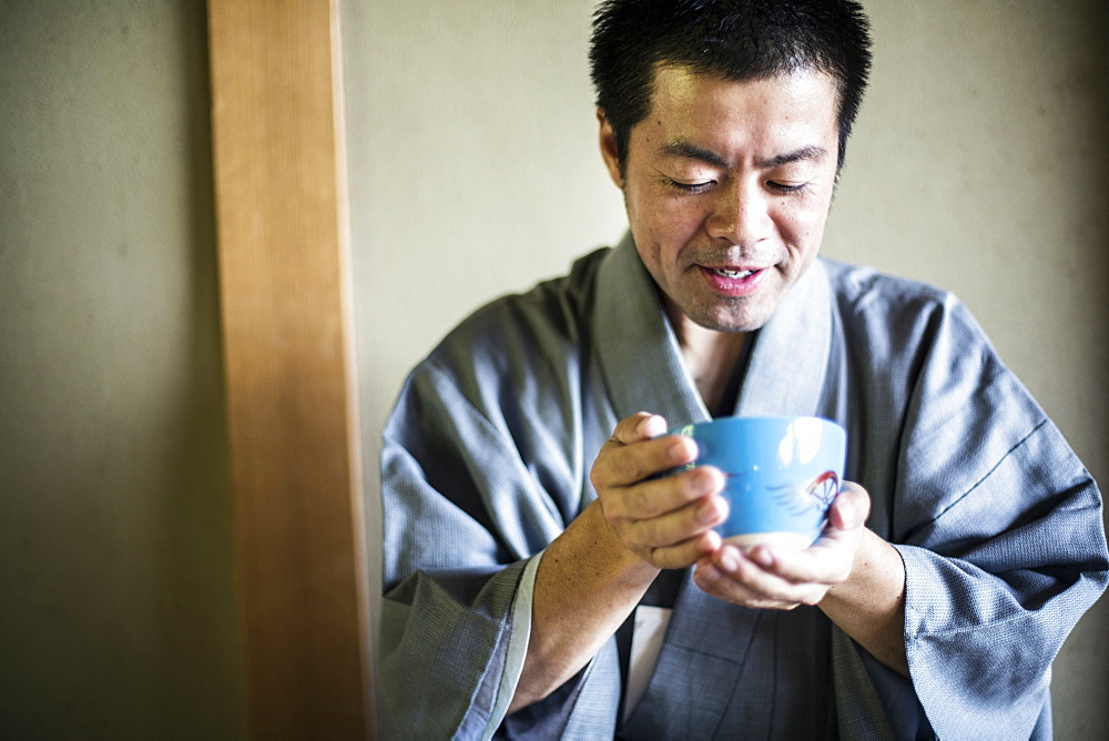 Japanese man wearing traditional kimono holding blue tea bowl during tea ceremony, Kyushu, Japan