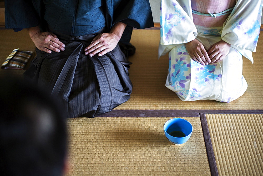 High angle view of Japanese man and woman wearing traditional white kimono with blue floral pattern kneeling on floor during tea ceremony, holding blue tea bowl, Kyushu, Japan