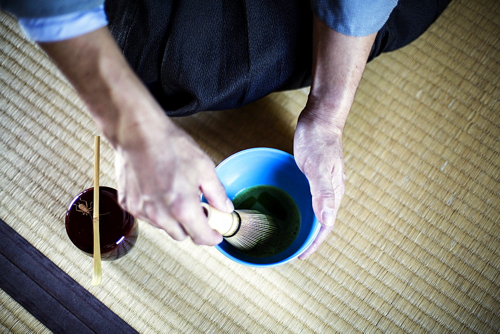 High angle close up of Japanese man wearing traditional kimono kneeling on floor using bamboo whisk to prepare Matcha tea in a blue bowl during tea ceremony, Kyushu, Japan