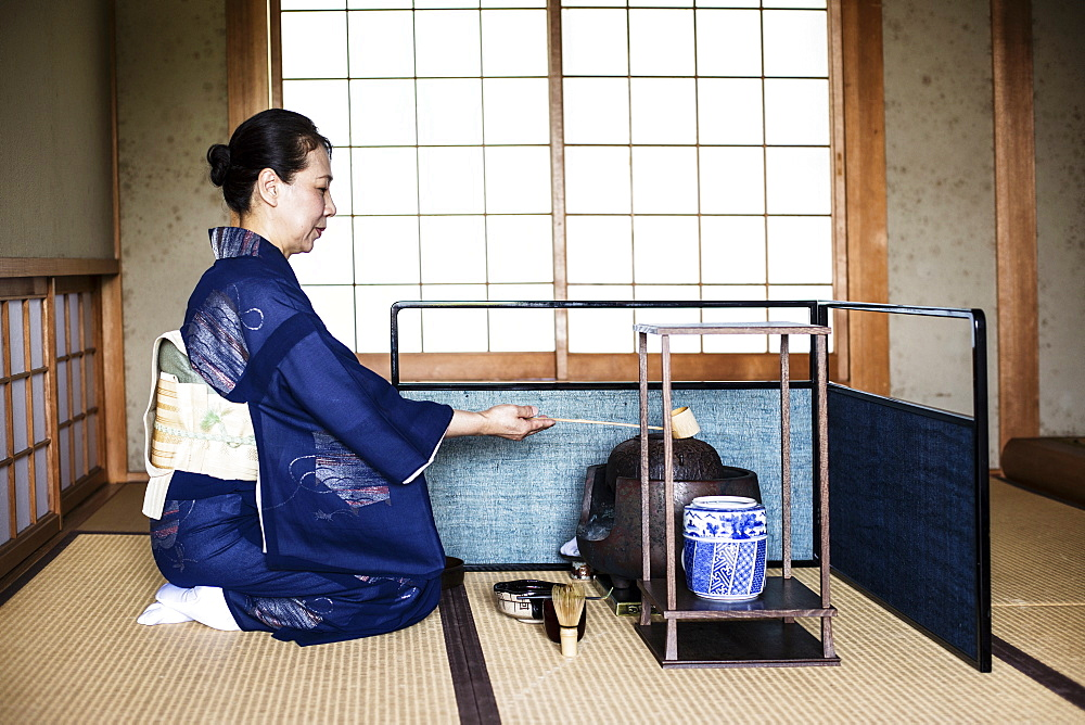 Japanese woman wearing traditional bright blue kimono with cream coloured obi kneeling on floor, using a  Hishaku, a bamboo ladle, during a tea ceremony, Kyushu, Japan