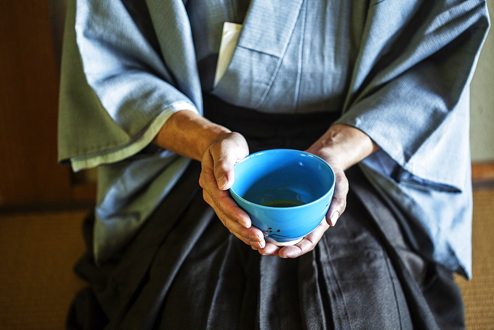High angle close up of Japanese man wearing traditional kimono kneeling on floor holding blue tea bowl during tea ceremony, Kyushu, Japan