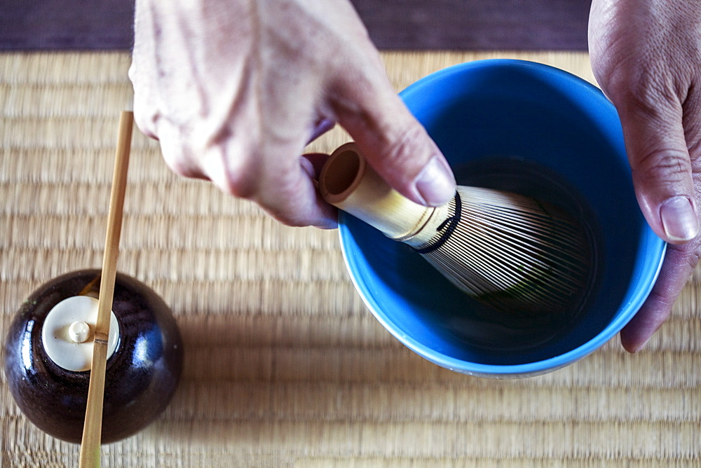High angle close up of person using bamboo whisk to prepare Matcha tea in a blue bowl during tea ceremony, Kyushu, Japan