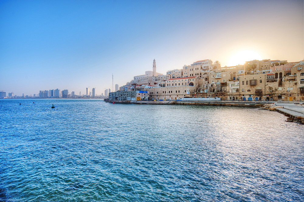 Sun rising over waterfront town, Israel, Israel