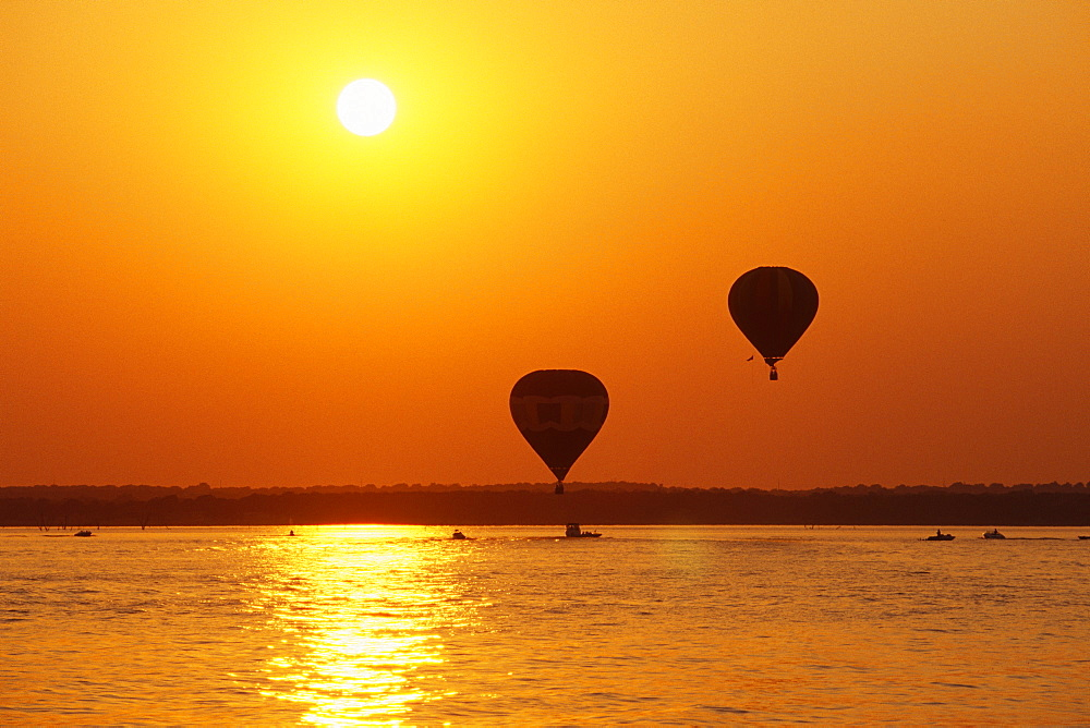 Hot Air Balloons Over Water at Sunset, Texas, United States of America