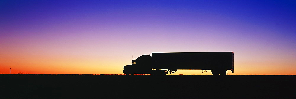 Silhouette of semi-truck against dramatic sky, Texas, United States of America