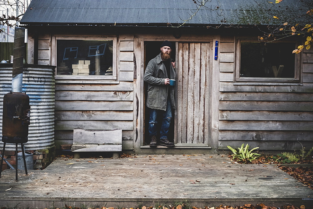 Bearded man standing in doorway of wooden workshop, holding blue mug, looking at camera, Berkshire, England