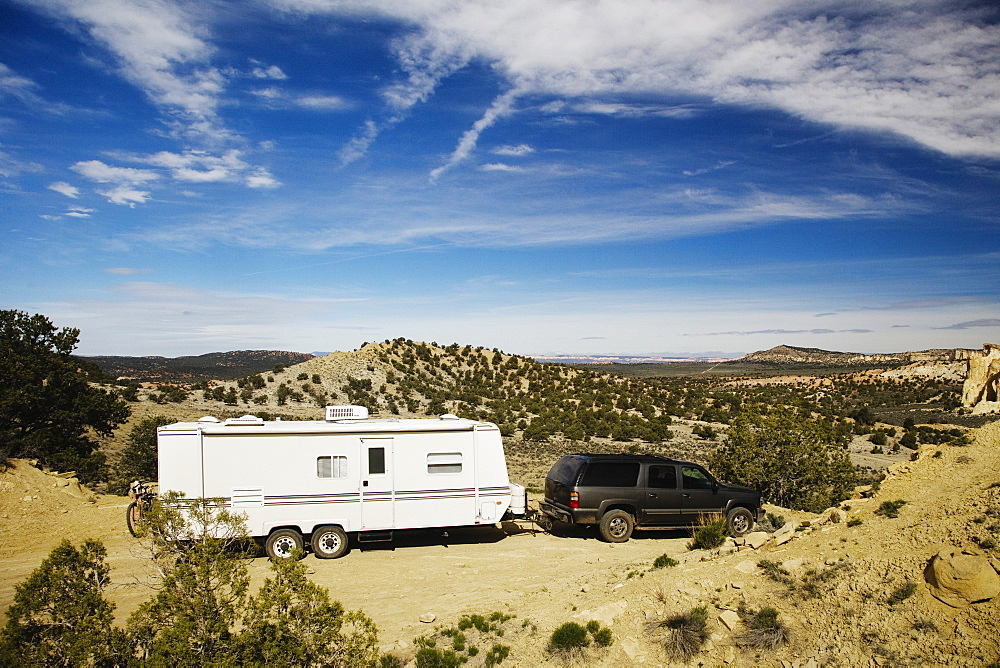 Car pulling trailer in desert landscape, Grand Staircase Escalante, Utah, United States, Grand Starcase Escalante, Utah, USA