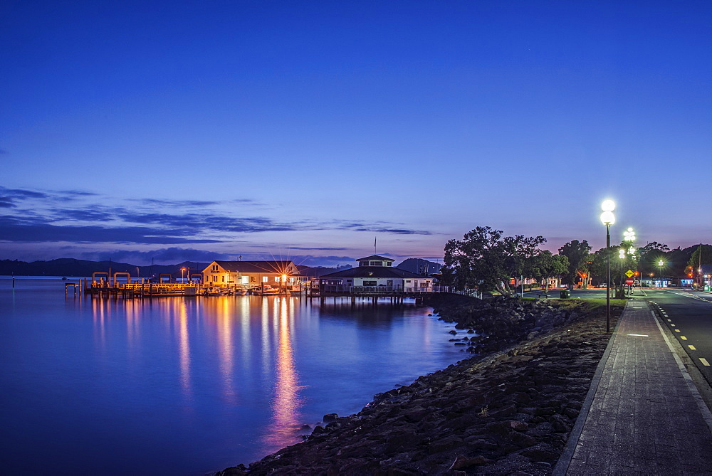 Illuminated buildings on water at dawn, Paihia, Paihia, New Zealand