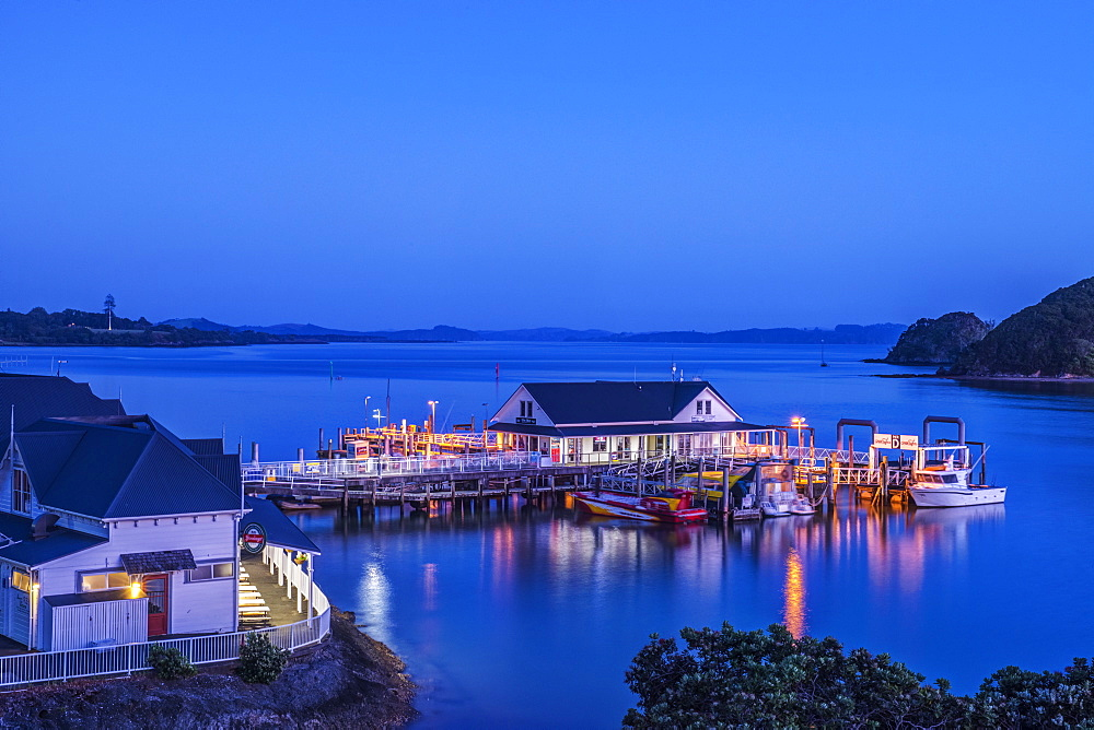 Illuminated building on water at dawn, Bay of Islands, Paihia, New Zealand