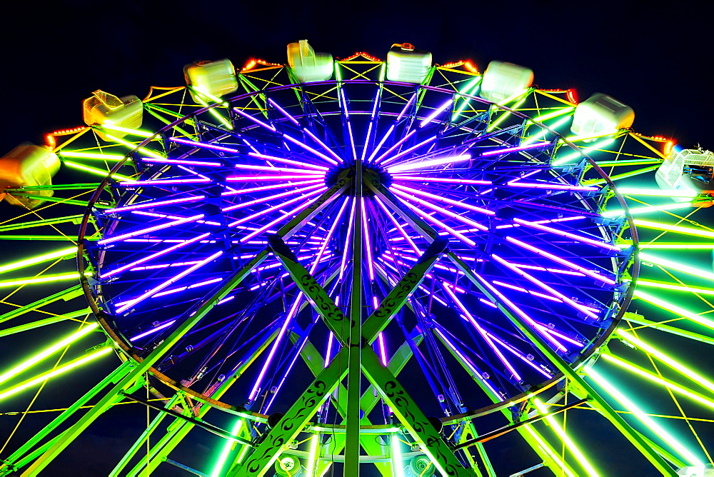 Neon Ferris Wheel ride at amusement park at night, Puyallup, Washington, USA