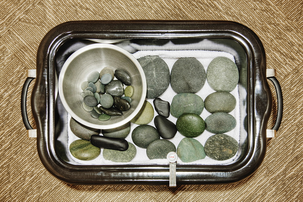 Hot stones and warmer on tray in spa