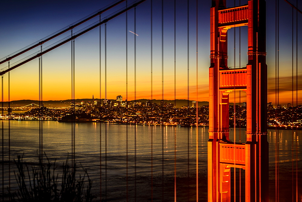 Golden Gate Bridge and San Francisco skyline lit up at night, San Francisco, California, United States