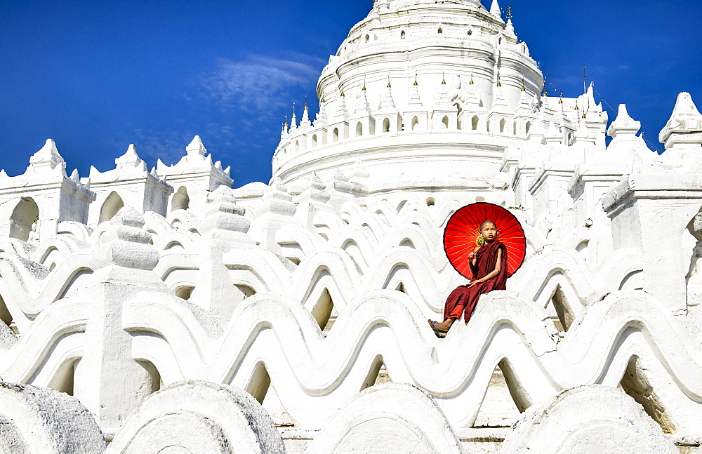 Asian woman sitting on temple walls, Mingun, Saigang, Myanmar