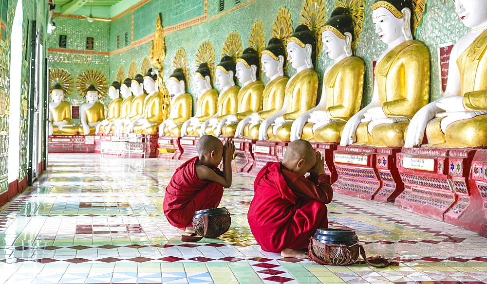 Asian Buddhist monks praying in temple, Mingun, Saigang, Myanmar