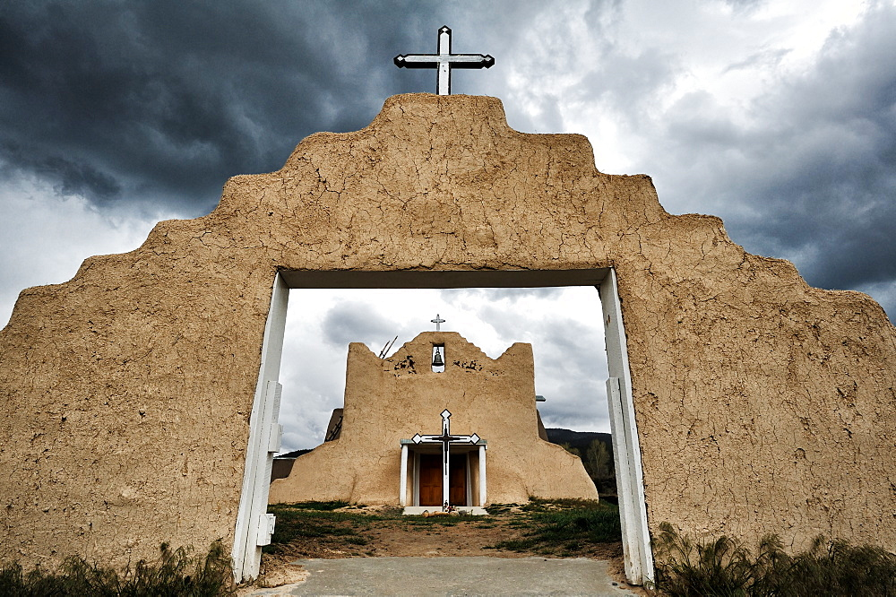Pueblo church archway under stormy sky, Picuris Pueblo, New Mexico, United States