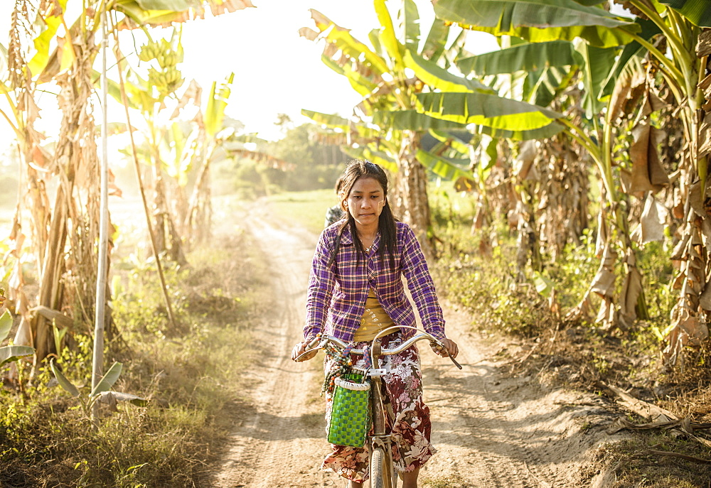 Asian woman riding bicycle on rural road