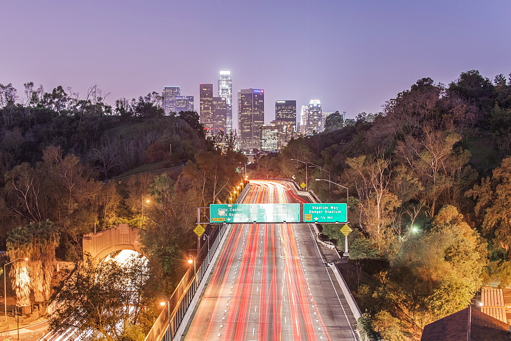 Los Angeles city skyline over busy highway illuminated at night, California, United States
