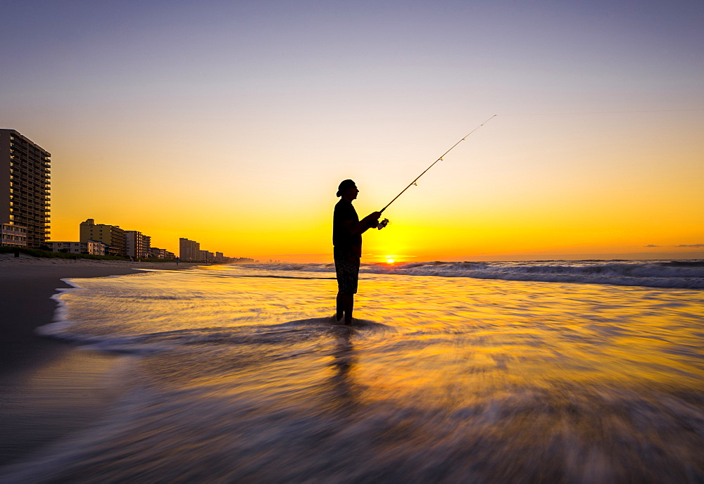 Blurred view of silhouette of man fishing in waves on beach at sunset