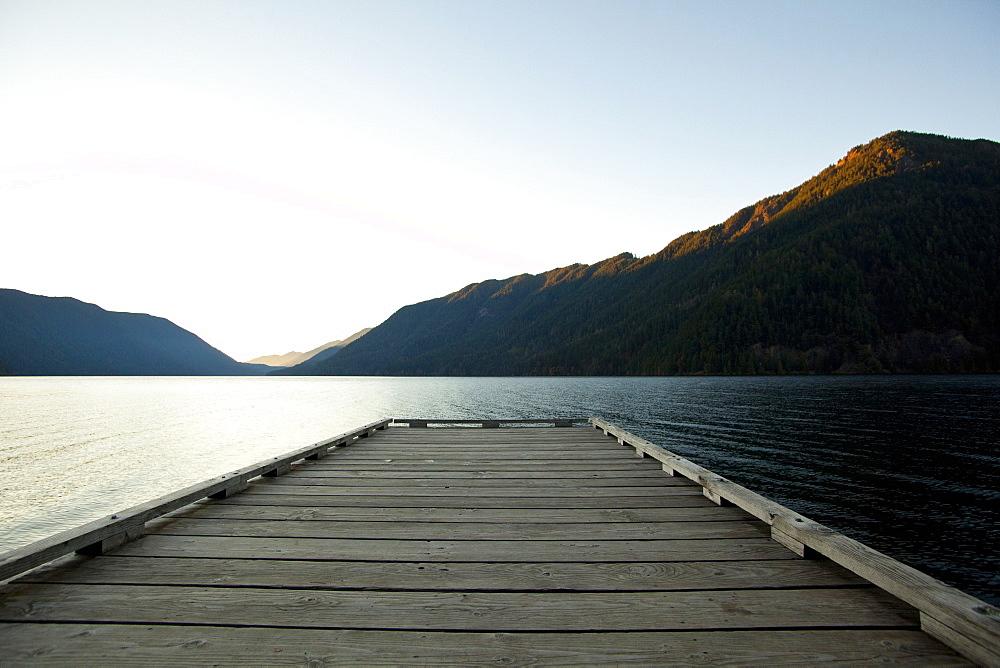 Wooden deck at lake under blue sky
