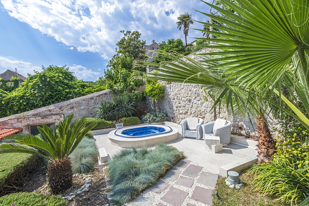 Soaking pool and armchairs on hillside patio