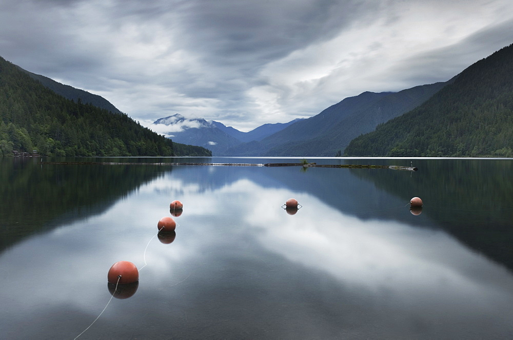 Buoys floating in still remote lake under clouds