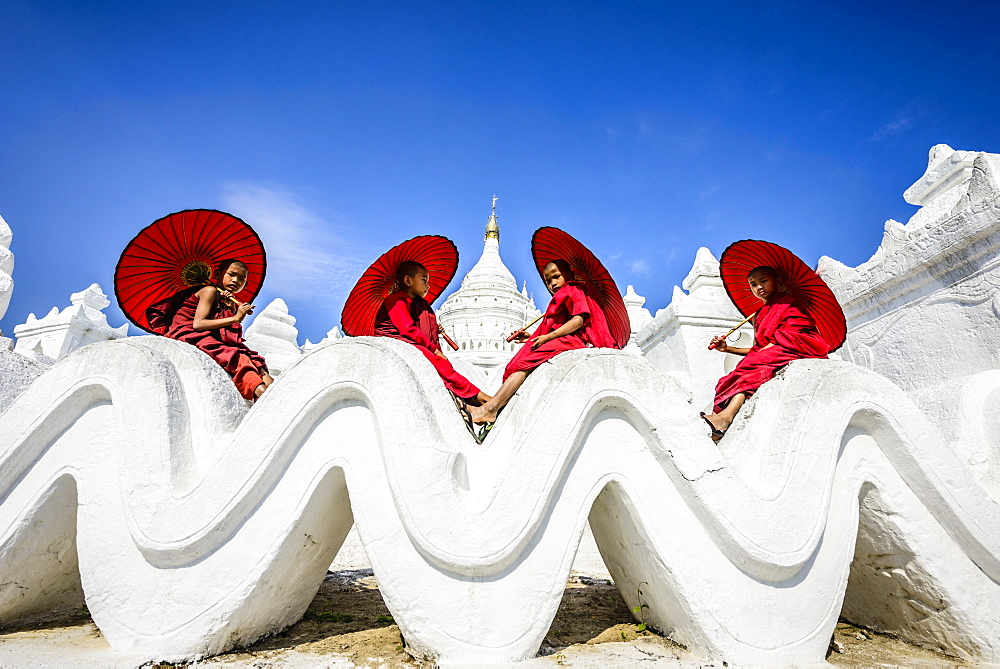 Asian monks sitting under umbrellas at historic temple, Mingun, Mandala, Myanmar