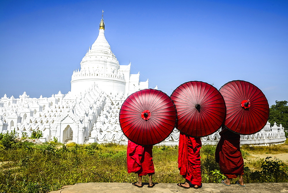 Asian monks under umbrellas viewing historic temple, Mingun, Mandala, Myanmar