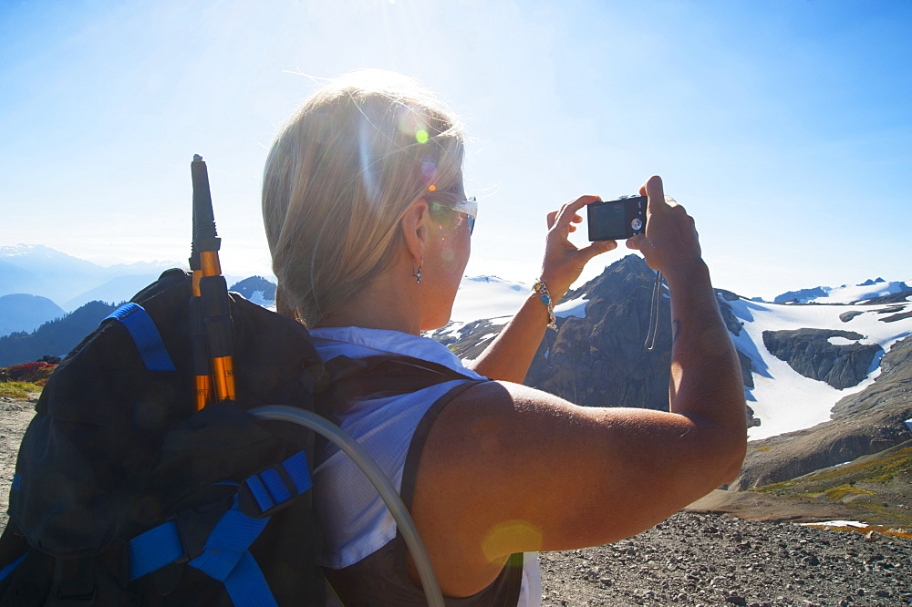Woman taking photograph of remote mountains