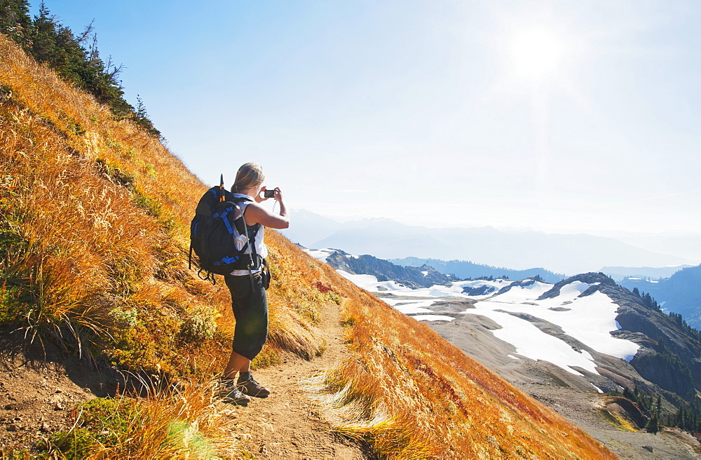Woman taking photograph of remote mountains on hillside