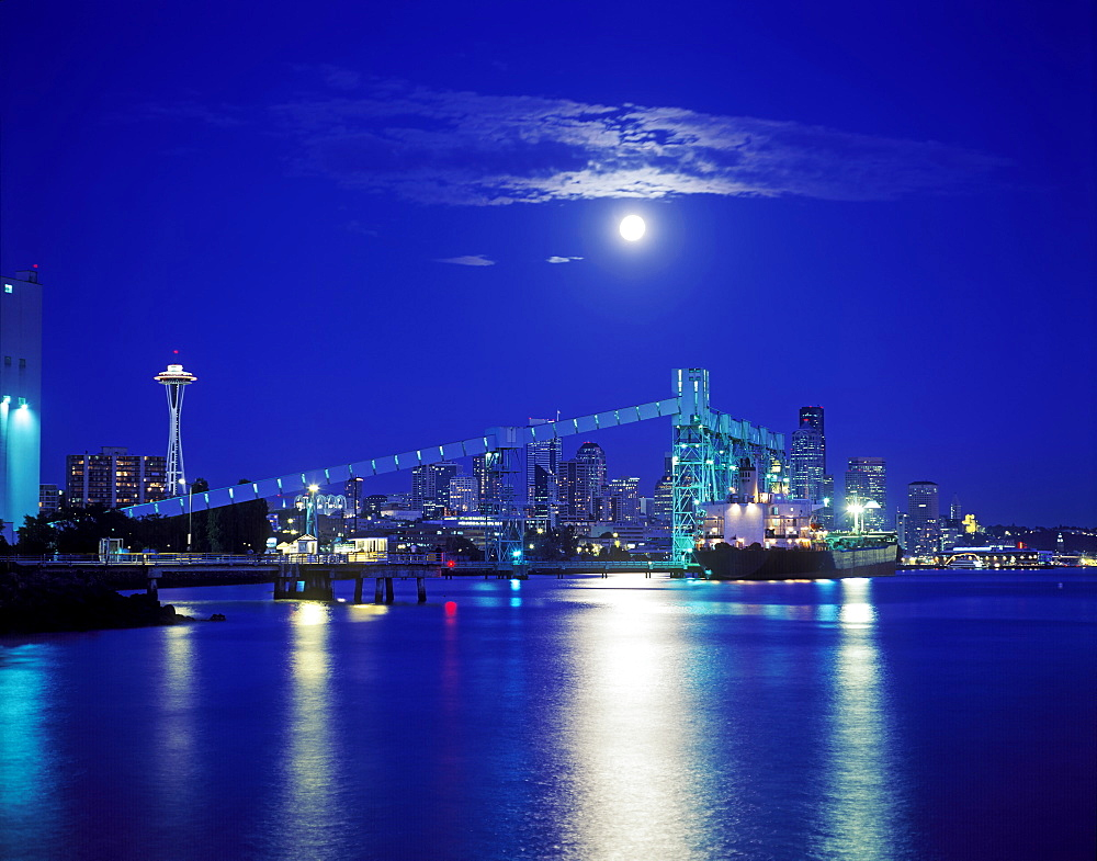 Moon over illuminated Seattle city skyline at night, Washington, United States