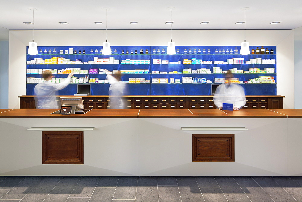 Blurred view of pharmacists behind counter in modern pharmacy