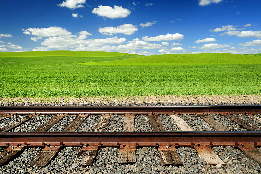 Railroad tracks and rolling hills in rural landscape