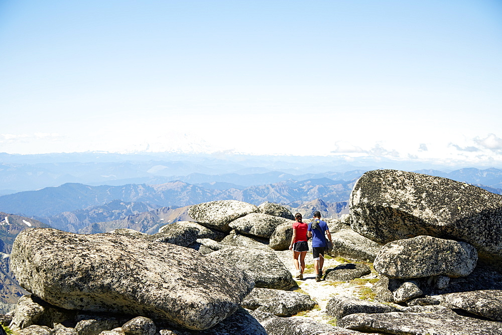 Couple hiking on rocky hilltop, Leavenworth, Washington, USA