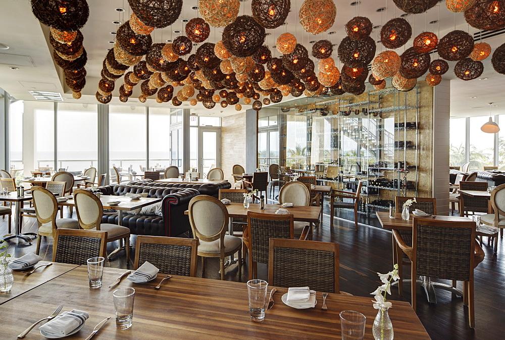 Lanterns over tables in modern restaurant, Miami, Florida, USA