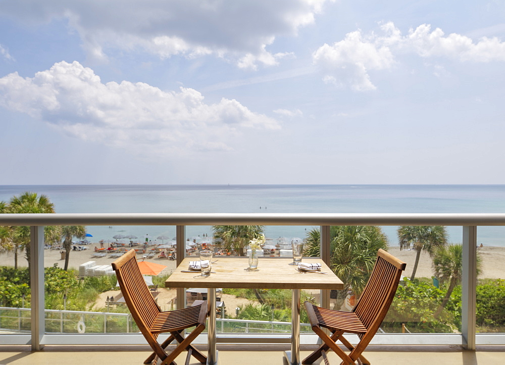 Empty table on restaurant balcony overlooking beach, Miami, Florida, USA
