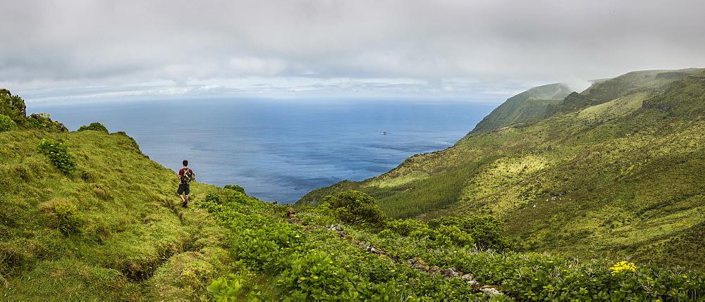 Hiker walking on hilltop path in rural landscape, Azores Islands, Flores, AzoresIslands