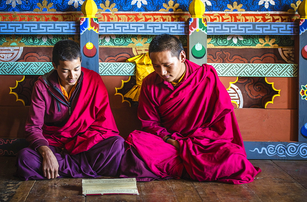 Asian monks reading on temple floor, Bhutan, Kingdom of Bhutan