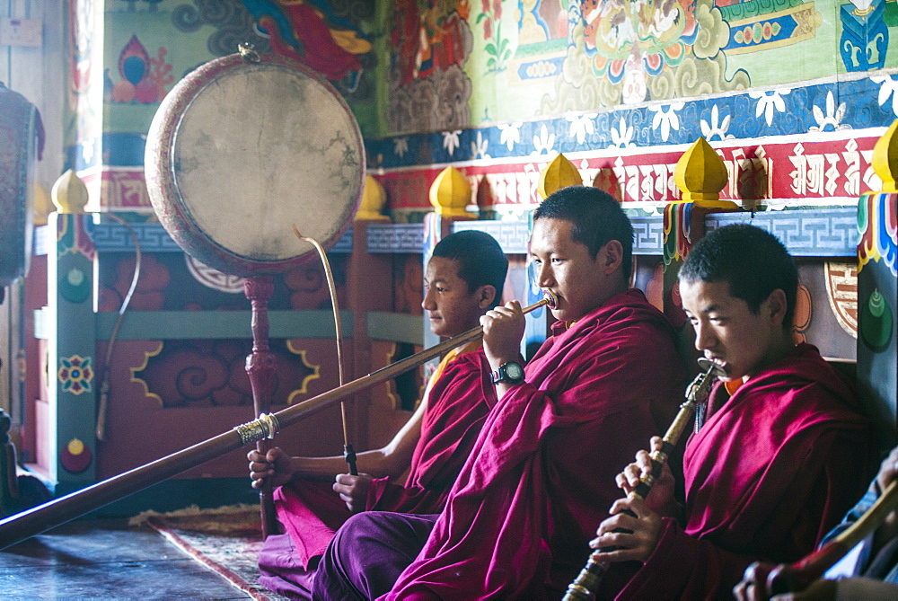 Asian monks playing instruments on temple floor, Bhutan, Kingdom of Bhutan