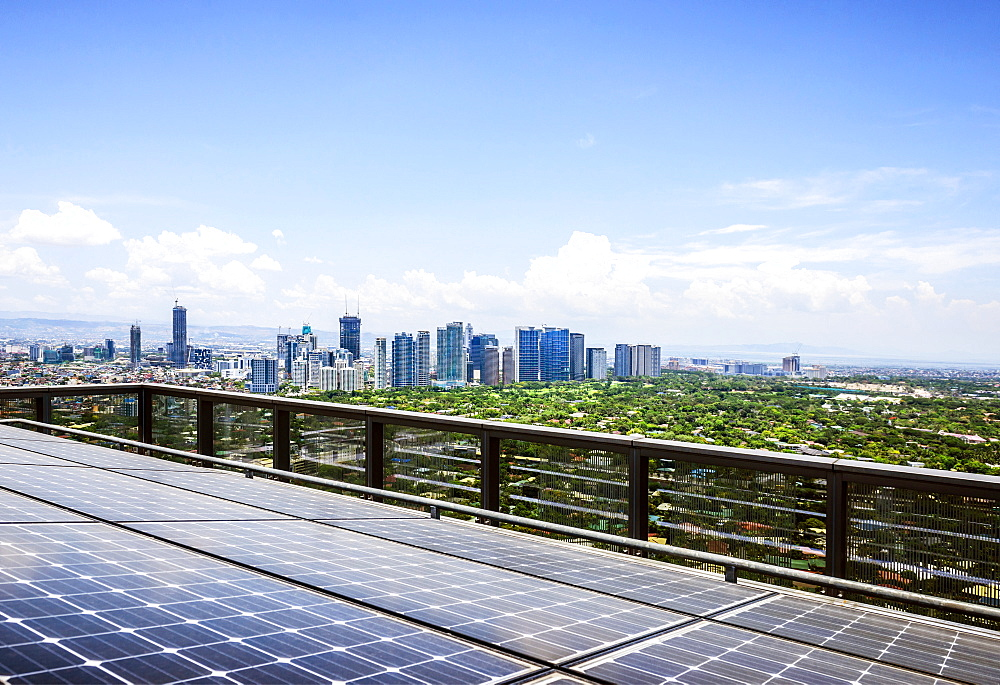 Solar panels and Manila cityscape under blue sky, Philippines, Manila, Philippines