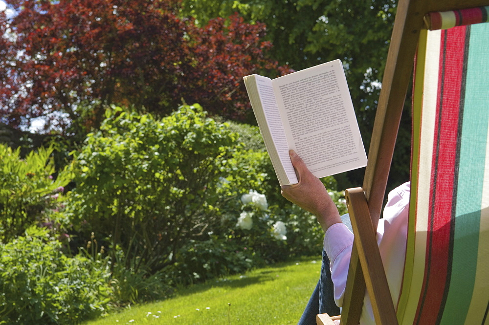 A person sitting in a deckchair, reading, Gloucestershire, England