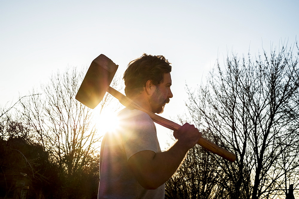 Bearded man walking outdoors at sunset, carrying large wooden mallet on his shoulder, Oxfordshire, England