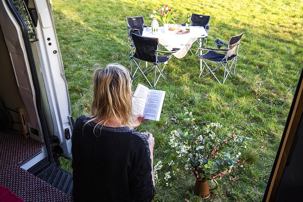 High angle rear view of woman sitting in door of camper van parked on a meadow, reading a book, Oxfordshire, England - 1174-6513