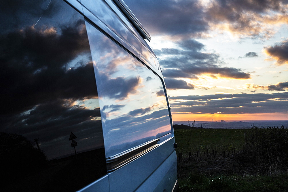 Reflections of clouds on camper van window at sunset, Oxfordshire, England