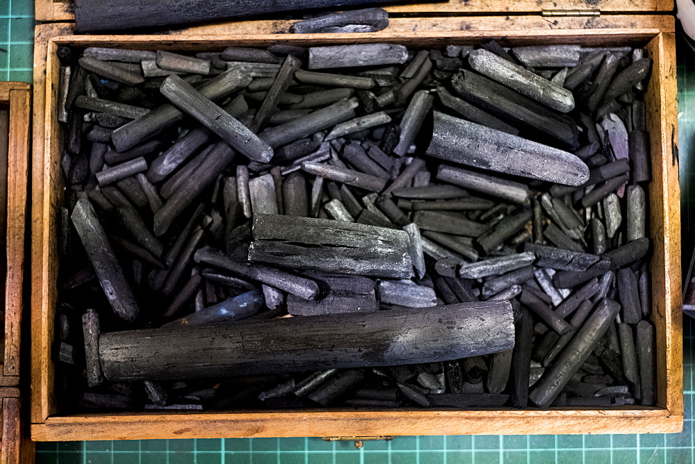 High angle close up of wooden box with a selection of artist's charcoal sticks in different sizes, Oxfordshire, England