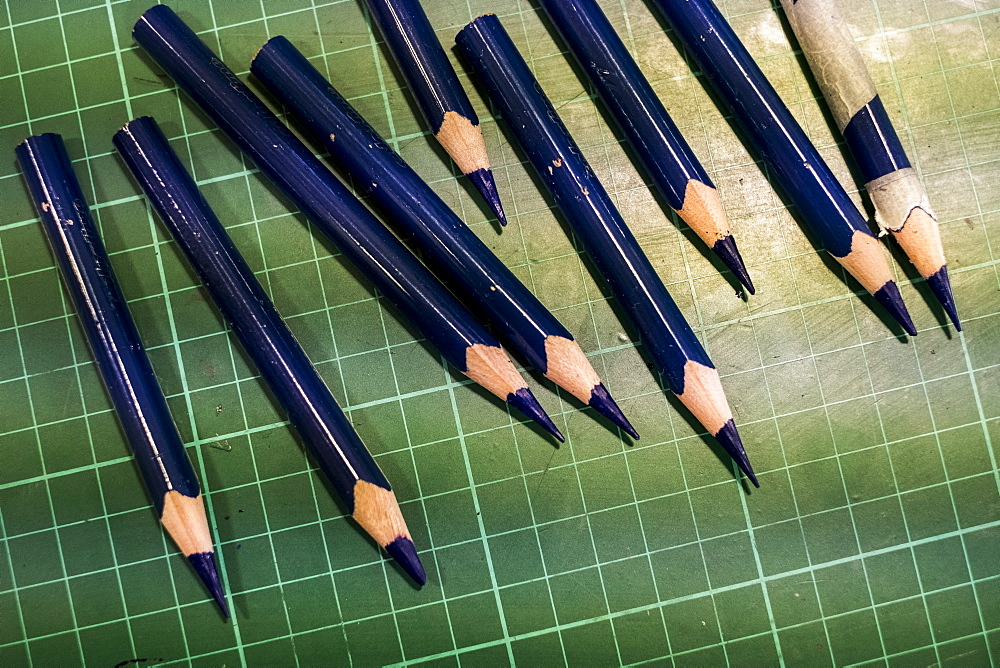 High angle close up of sharpened blue pencils on green cutting mat, Oxfordshire, England