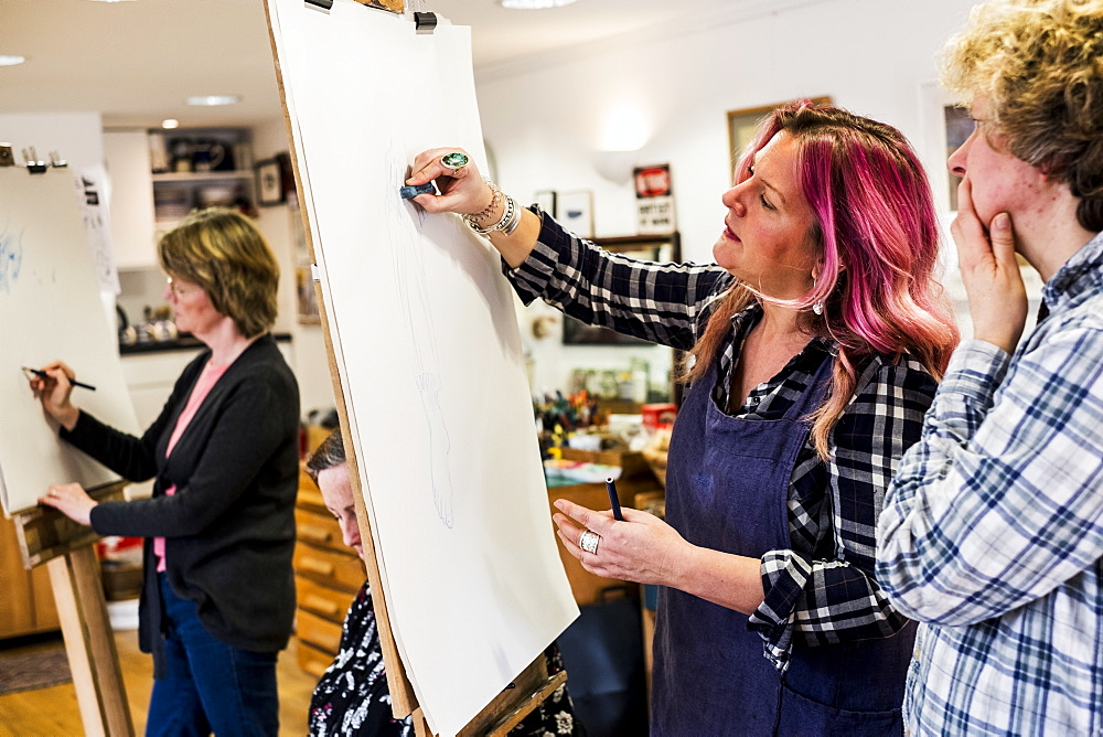 Woman standing at an easel, drawing a human leg at a life drawing glass, Oxfordshire, England