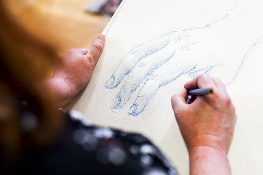 High angle close up of artist drawing human hand, Oxfordshire, England