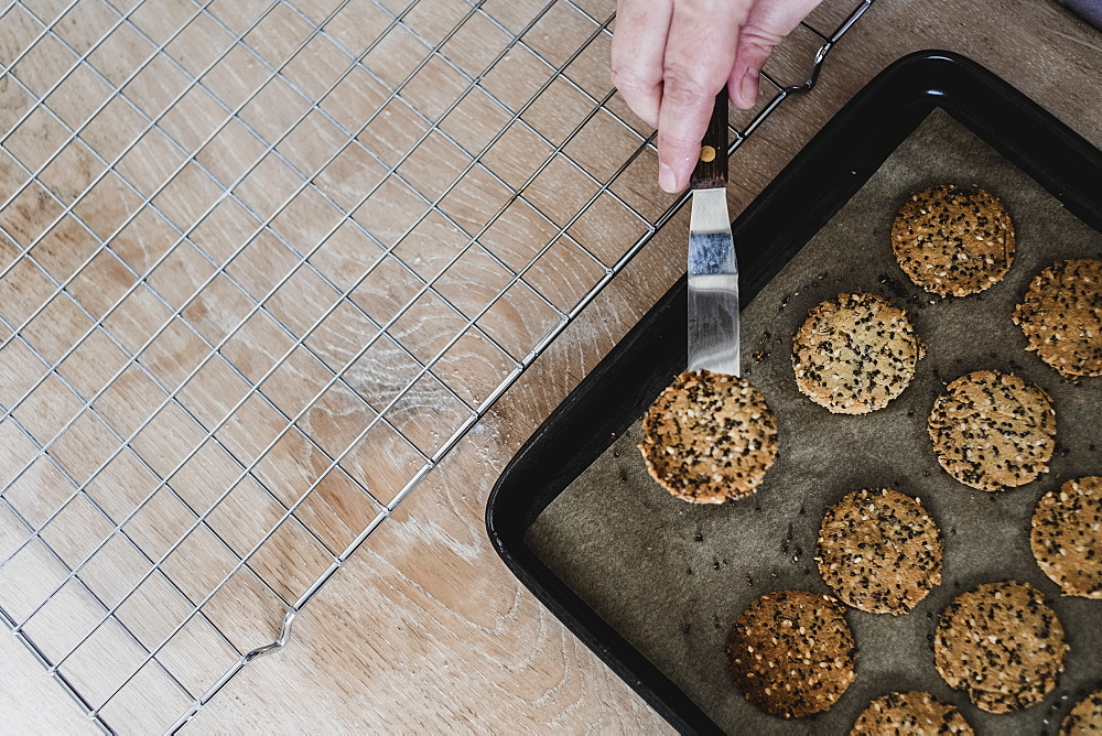 High angle close up of person removing freshly baked seeded crackers from a baking tray, England
