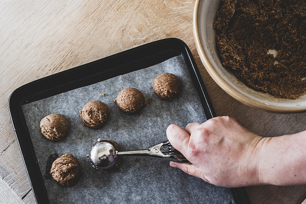High angle close up of person putting chocolate cookie dough on a baking tray, England