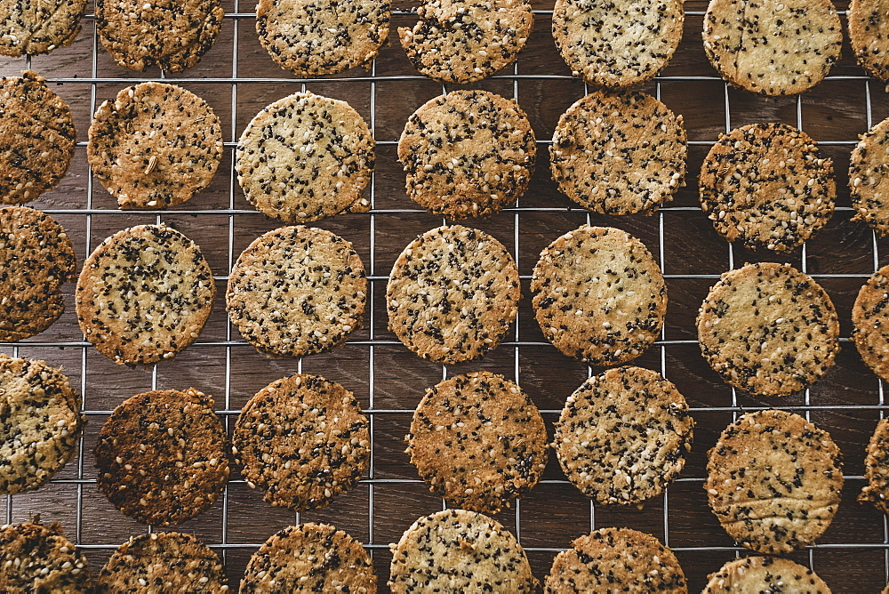 High angle close up of freshly baked seeded crackers on a baking tray, England